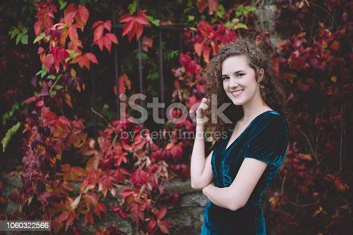 Beautiful smiling brunette in a stylish dark blue velvet dress in an autumn park