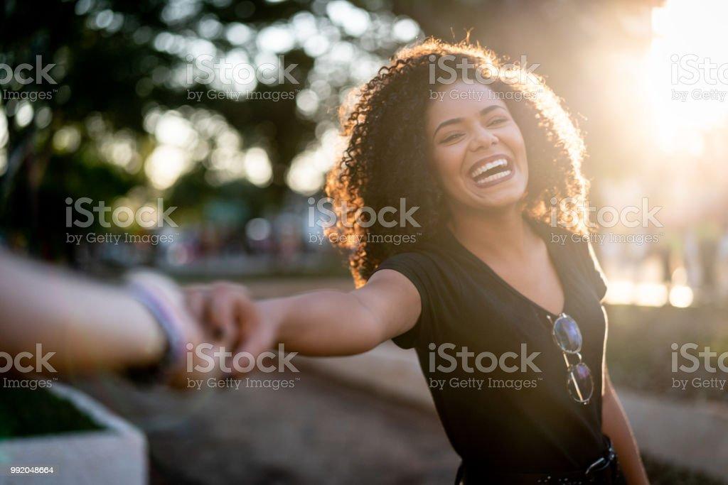 Beautiful Curly Hair Woman Holding Hands/Following Boyfriend stock photo