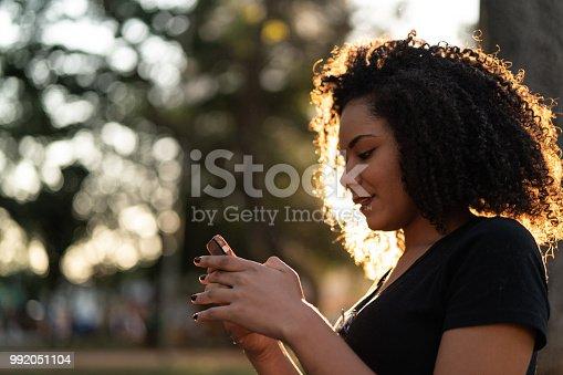 946192604 istock photo Beautiful Curly Hair Woman Using Mobile 992051104