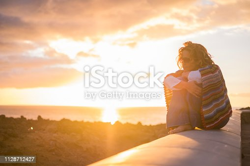 Beautiful curly woman sitting on a wall and enjoy the sunset time feeling the freedom sensation on her skin and feed with nice thoughts her mind - mexican casual style and hippy concept