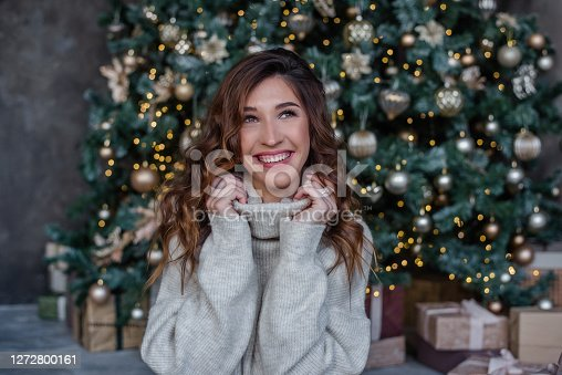 A beautiful curly-haired girl, wrapped in the collar of a gray sweater and smiles openly. A close-up portrait of a model looking at the camera. The background of a Christmas tree with toys, lights.
