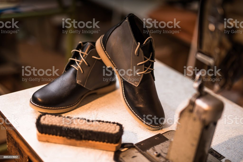 Beautiful custom made leather shoes next to sewing machine. stock photo