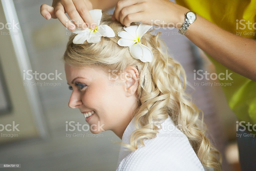 Beautiful, cute blond bride doing hair with flowers before wedding. stock photo