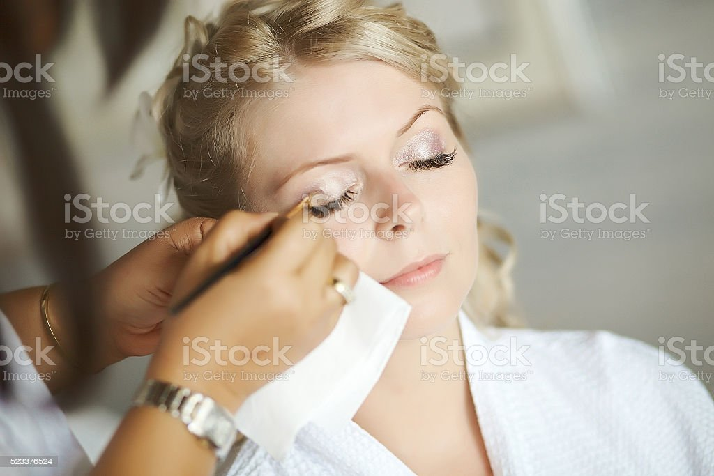 Beautiful, cute blond bride doing makeup before wedding day. stock photo