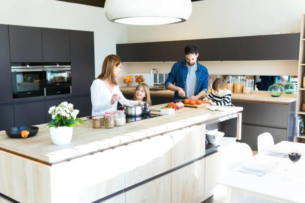 schöne niedliche familie, die spaß beim gemeinsamen kochen in der küche zu hause. - chefkoch auflauf stock-fotos und bilder