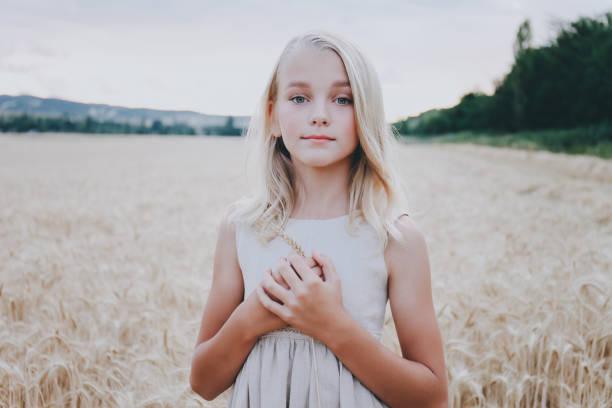 Beautiful cute girl in a wheat field. stock photo