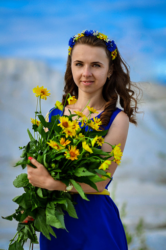 674214372 istock photo Beautiful cute girl in blue dress with bouquet of yellow 507629478