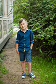 A beautiful cute little boy in a blue shirt and dark shorts in the summer stands near the bushes, looks at the camera. Stylish portrait, vertical photo
