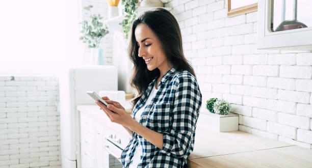 hermosa mujer sonriente linda está utilizando el teléfono inteligente en la cocina en casa. - sin personas fotografías e imágenes de stock