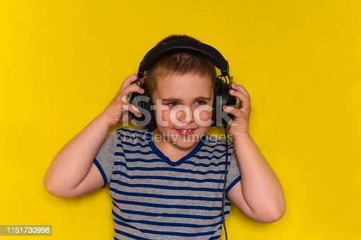 istock beautiful cute young boy  with  big black headphones isolated on yellow vibrant background 1151730998