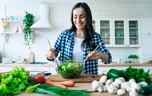 Beautiful cute young smiling woman on the kitchen is preparing a vegan salad in casual clothes.