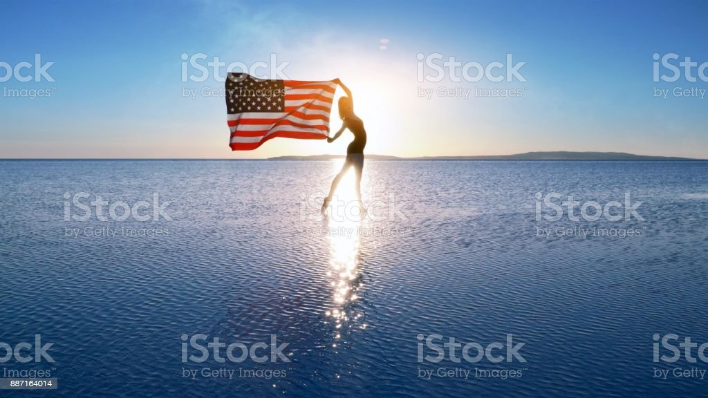 Beautiful dancer holding a US flag on the lake. stock photo