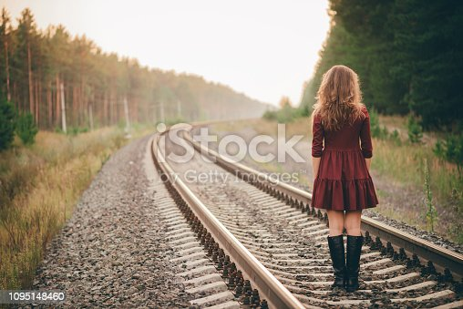 Beautiful dancing girl with curly natural hair enjoy nature in forest on railway. Dreamer lady in burgundy dress walk on railroad. Back view on inspired girl on rails at dawn. Sun in hair in autumn.