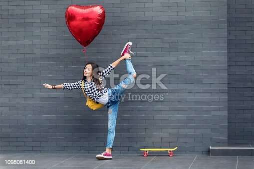 Beautiful teenage girl with heart shape balloon and skateboard in front of gray wall.