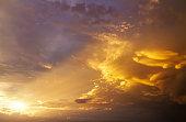 Beautiful dark fluffy cloudy sky with sun rays. Sunset light.