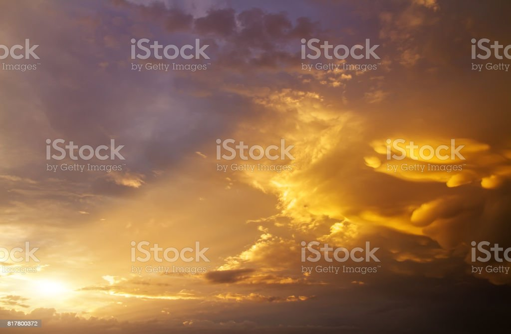 Beautiful dark fluffy cloudy sky with sun rays. Sunset light. stock photo