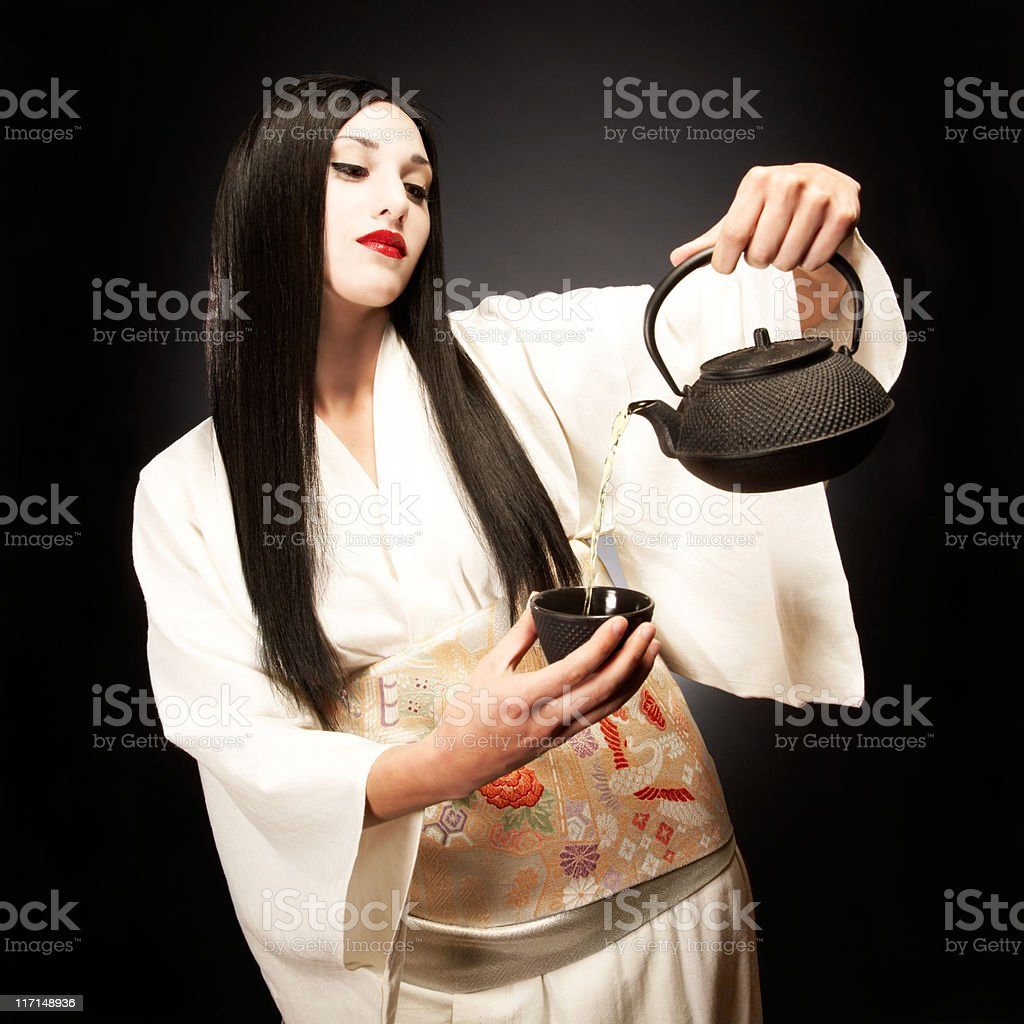 Beautiful Dark Haired Young Woman Dressed as Geisha Pouring Tea royalty-free stock photo