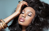 Beautiful dark model with golden jewelry over cyan background. Fashion and beauty with African dark skin model.