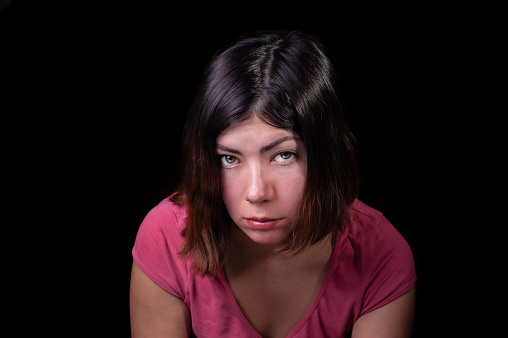 117149457 istock photo beautiful dark-haired girl with green eyes in a pink t-shirt with a serious sad look on an isolated black background 1213870448