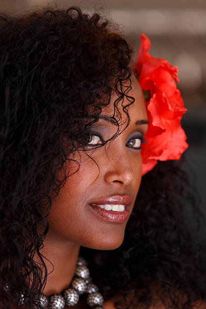 beautiful dark-haired young woman with red flower - eritrea stock photos and pictures
