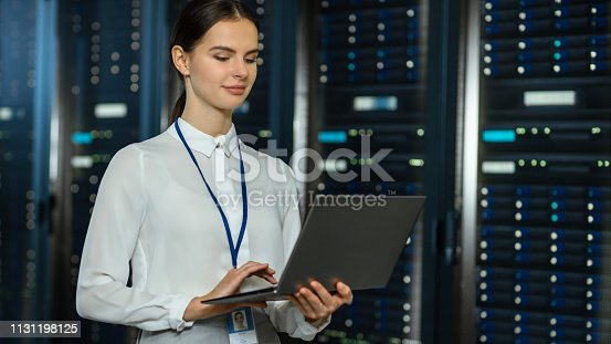 1131198396istockphoto Beautiful Data Center Female IT Technician Standing Near Server Rack Corridor with a Laptop Computer. She is Using Notebook and Working with Servers. 1131198125