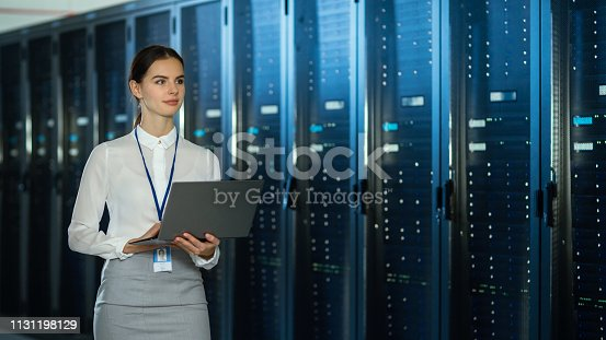 istock Beautiful Data Center Female IT Technician Walking Through Server Rack Corridor with a Laptop Computer. She is Visually Inspecting Working Server Cabinets. 1131198129