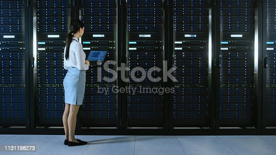 1131208605 istock photo Beautiful Data Center Female IT Technician Walking Through Server Rack Corridor with a Laptop Computer. She Stops and Visually Inspects Working Server Cabinets. 1131198273