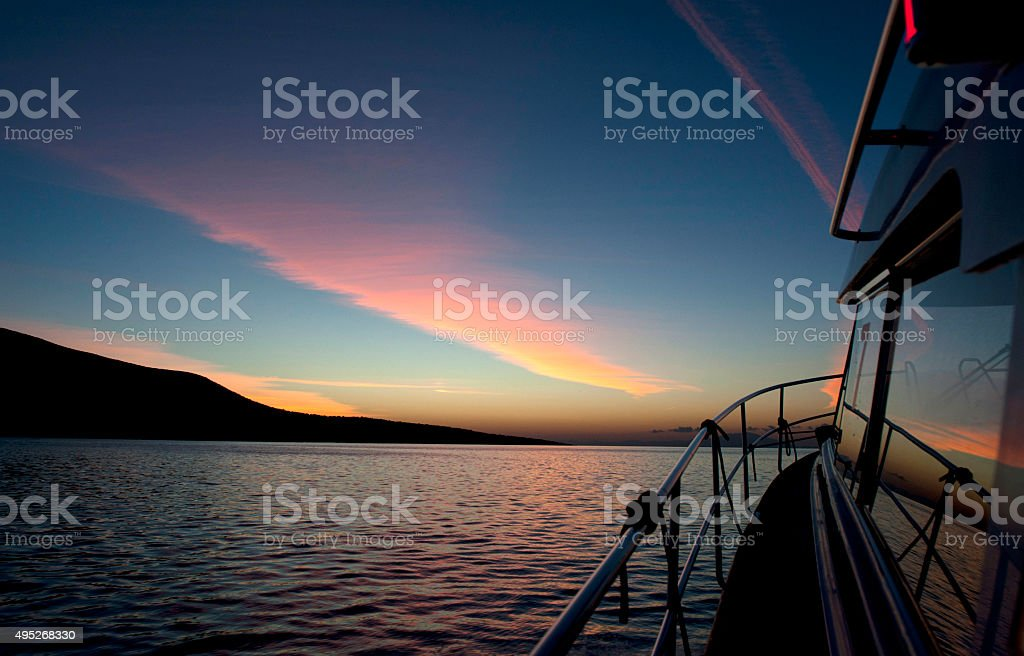 beautiful dawn on the sea and motorbat's bow stock photo