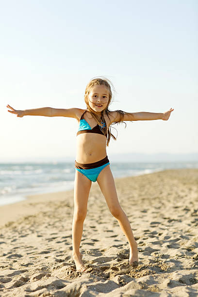 beautiful day at the beach - girl alone in swimsuit stock photos and pictures