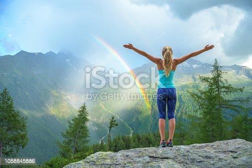 Young woman enjoying a colorful rainbow in the mountains during a summer rain