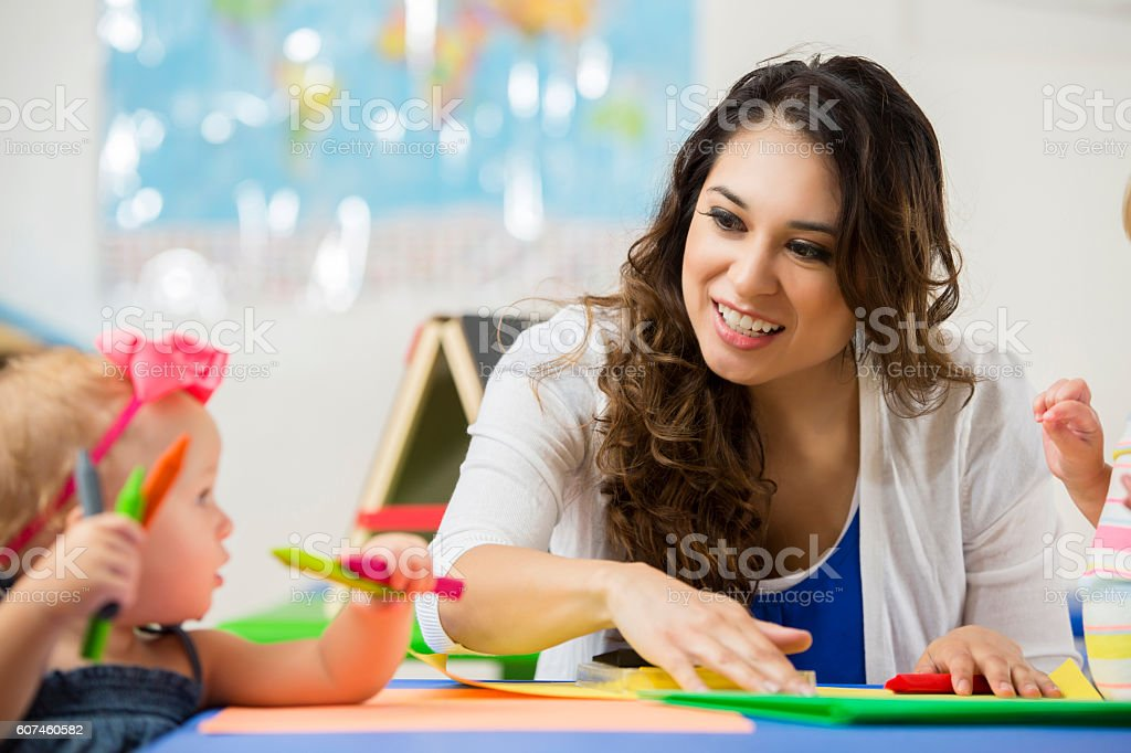 Beautiful daycare teacher helps toddler with coloring project stock photo