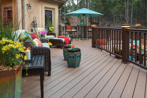 Beautiful backyard deck with built-in lighting and fully decorated with vibrant and colorful furniture and decor