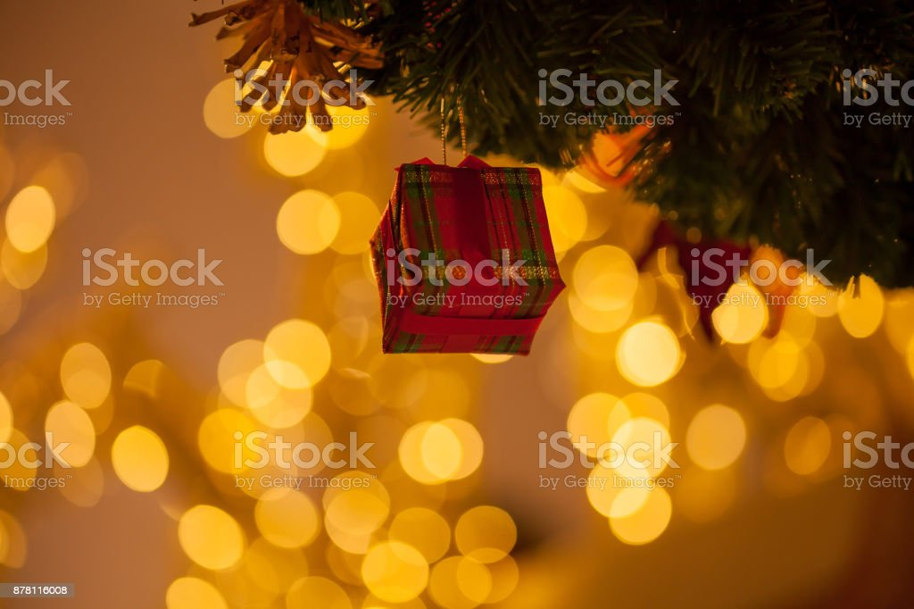 Beautiful decorated Christmas tree background with red gift box and xmas ornaments in close-up shot stock photo