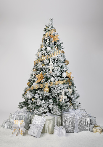 Beautiful decorated christmas tree in gold and white colors in front of a white background.