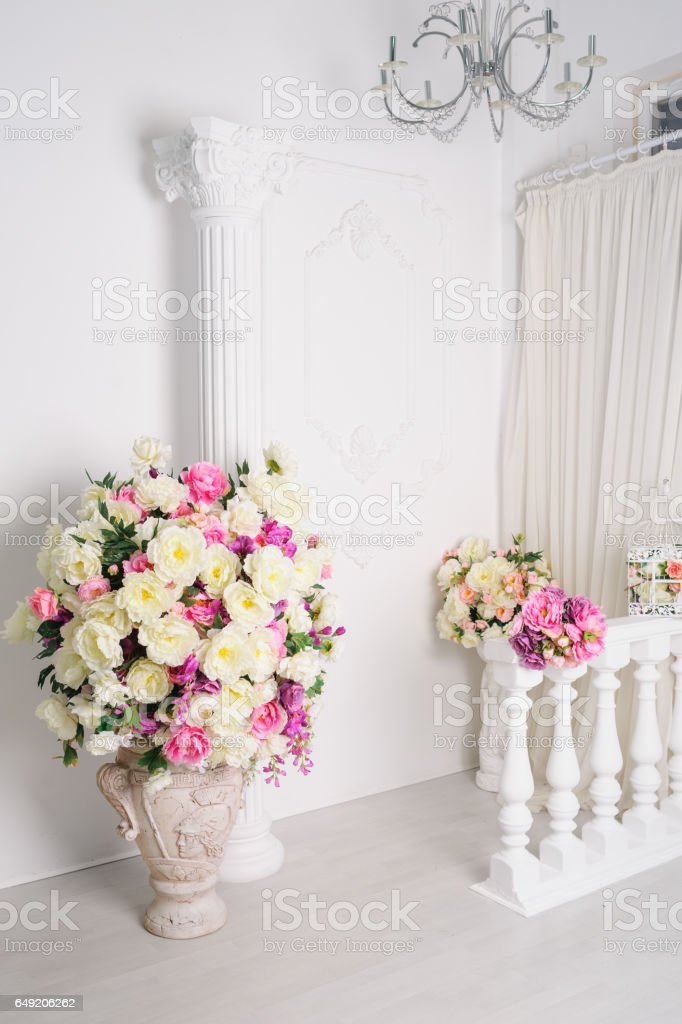 Beautiful Decoration Of Flowers In Vases In White Studio Stock Photo
