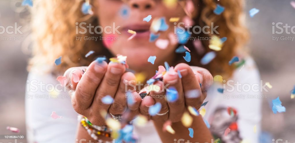beautiful defocused woman blow confetti from hands. celebration and event concept. happiness and colored image. movement and happiness having fun stock photo