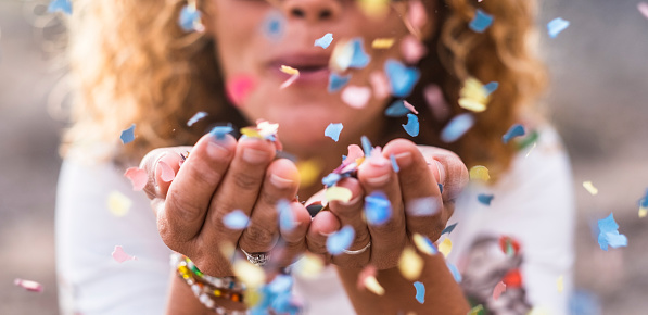 Beautiful Defocused Woman Blow Confetti From Hands Celebration And Event Concept Happiness And Colored Image Movement And Happiness Having Fun - Fotografias de stock e mais imagens de 40-49 Anos