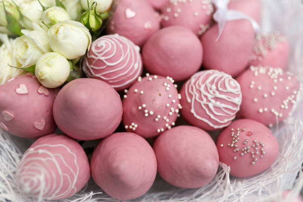 Beautiful delicate bouquet consisting of strawberries in pink chocolate and white roses on a black background. Close-up stock photo