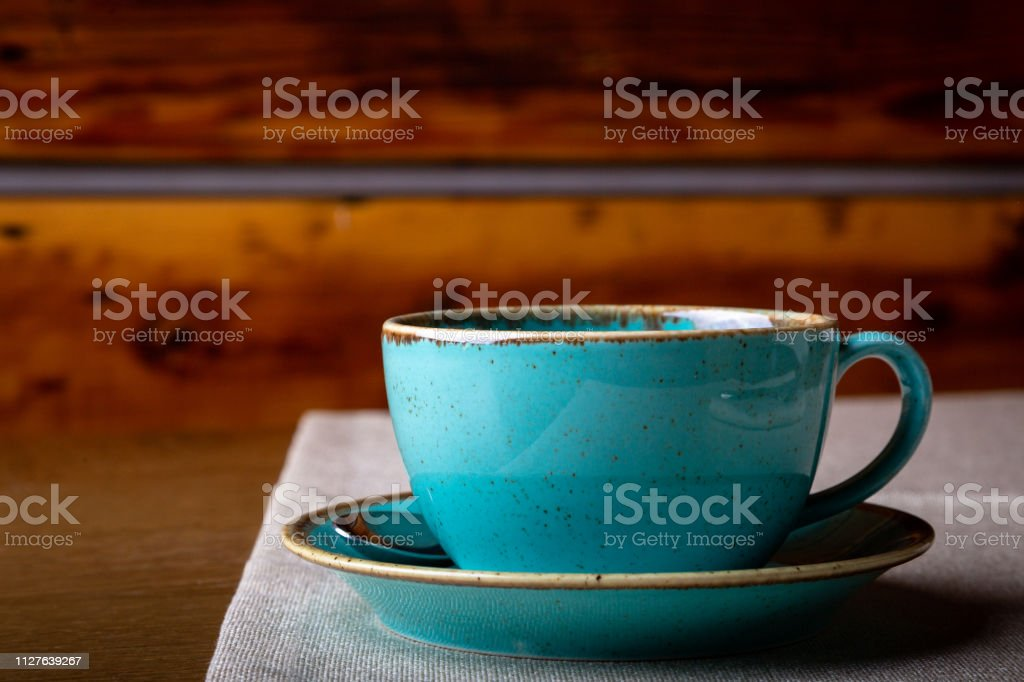 Beautiful Delicious Latte art, Blue coffee cup on wooden background