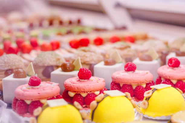 prachtige heerlijke gebakjes met frambozen op een showcase in een franse winkel. - deeggerechten stockfoto's en -beelden
