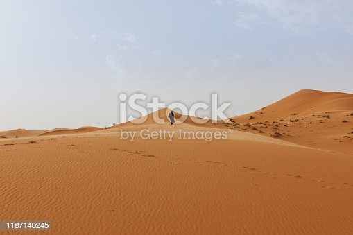 Desert dunes landscape with a berber man walking in the background