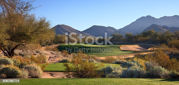A beautiful desert golf course. Scottsdale, Arizona, United States. The American southwest is home to some of the most spectacular golf courses in the world. This is a golf course scenic image taken in fall with the cottonwoods in beautiful yellow and gold colour. Nobody is in the image, taken with Canon Mark II camera body and L series lens. Par 3 golf hole. Panorama.
