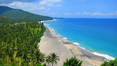 Beautiful deserted rural and lush Lombok beach Pantai Nipah with crystal blue waters and coconut trees