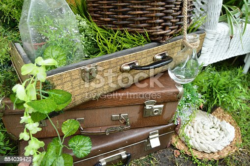 istock Beautiful design in the Park - vintage suitcases with bottles, plates and basket on grass 884039472