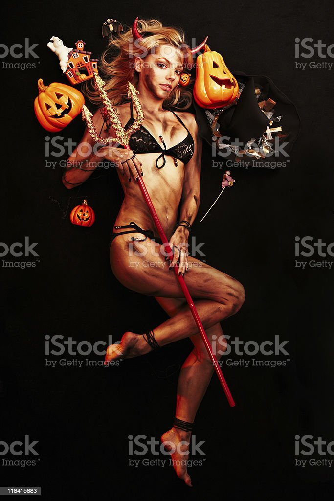 Beautiful devil with trident and Halloween accessories on black royalty-free stock photo