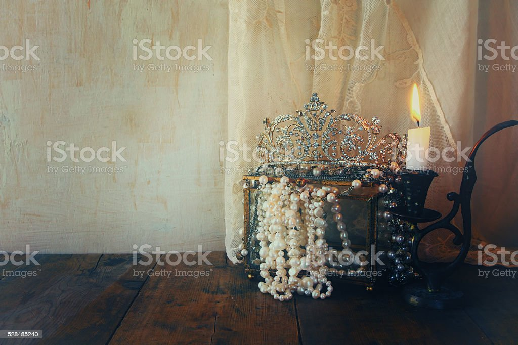 beautiful diamond queen crown, white pearls next to burning cand stock photo