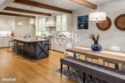 istock beautiful dining room and kitchen in new luxury home with hardwood floors, island, pendant lights, and glass fronted cabinets 680300296
