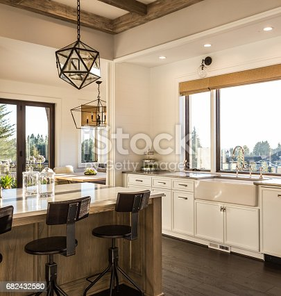 istock beautiful dining room and kitchen in new luxury home with island and pendant light fixtures 682432580