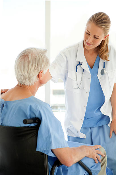 Beautiful doctor consoling senior patient stock photo