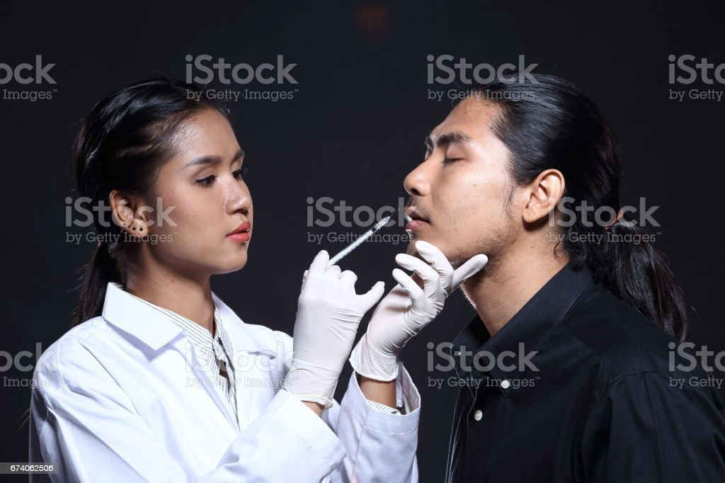 Beautiful Doctor inject beauty chemical to cheek, chin, eyebrow, forehead by syringe needle to handsome patient royalty-free stock photo